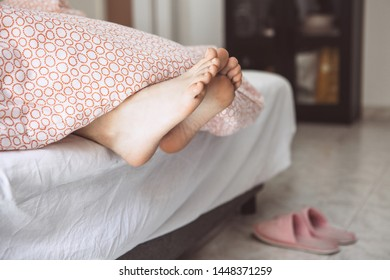 Legs of young adult girl under the blanket close up. She is sleeping. Near slippers on the floor