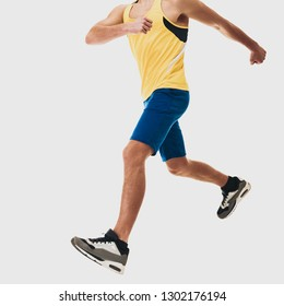 legs of Young athletic guy in sportswear running on white background