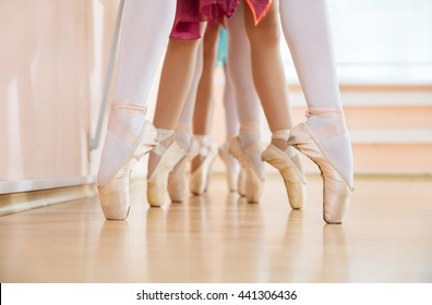 Legs of young ballerinas standing on pointe in row, ballet dancing class