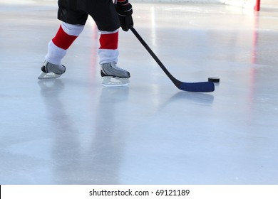 Legs of young child playing outdoor pond hockey