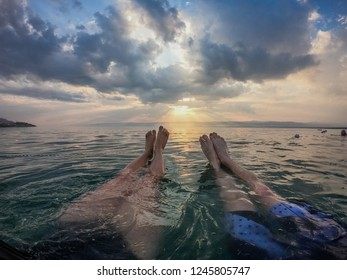 Legs of a young couple pointed into sunset in a Dead Sea while floating on water.