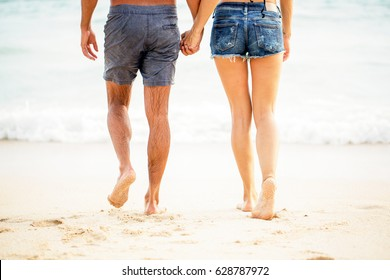Legs of young couple walking on sand at seaside