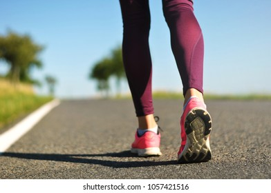 Legs of a young female runner on a road while jogging