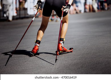 legs young girl athlete in ski-roller rides on asphalt