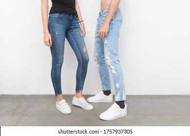 Legs in young girl in black shirt with blue jeans and man in torn blue jeans with black sneaker,shoes