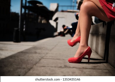 Legs of young girl with red high-heeled shoes in the city