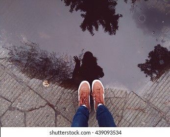 Legs of young hipster girl in brown leather sneakers standing near big puddle. Reflection of hello gesture. Mobile photo.