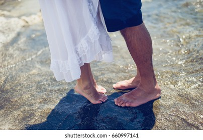 Legs of young lovely couple on the sea coast