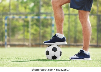Legs of young man with ball on soccer pitch
