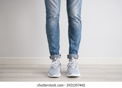 Legs of a young man in jeans and sneakers on gray background.