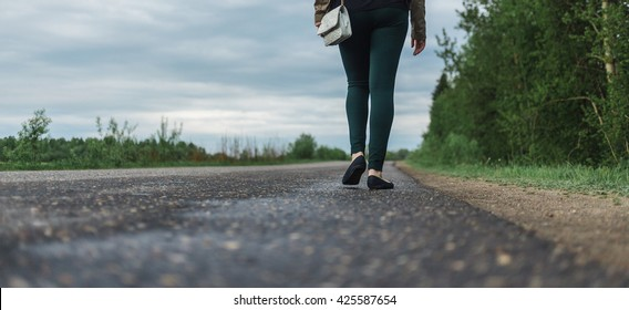 Legs of young woman in casual wear walking the forest road. concept of loneliness, uncertainty, choice