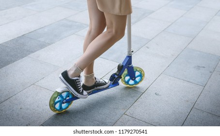 Legs of young woman on kick scooter at street.