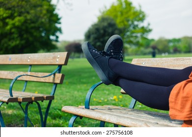 The legs of a young woman as she is lying on a bench in the park relaxing