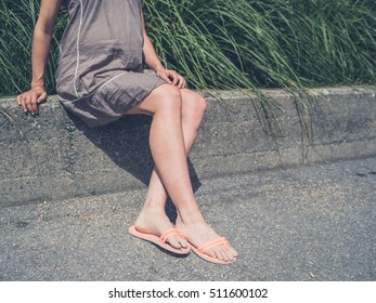 The legs of a young woman as she is sunbathing and sitting outside