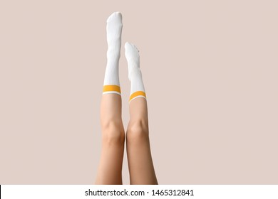 Legs of young woman in socks on light background