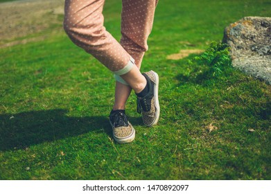 The legs of a young woman standing in nature on a sunny summer day