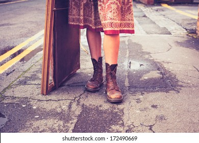 The legs of a young woman standing in the street with picture fr