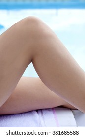 Legs of young woman sun tanning beside swimming pool