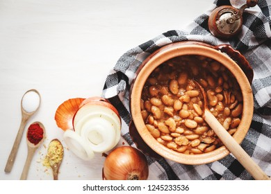 Legume lunch. Top view of beans inside earthen vessel, surrounded by spices and ingredients, against white wooden board.