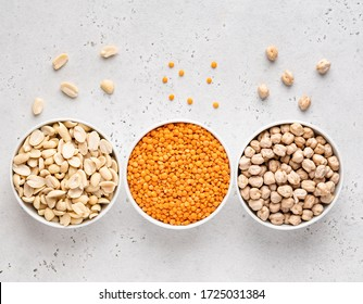 Legumes assortment. Red lentils, peanuts, chickpeas in white ceramic bowls. Natural and vegetarian protein food. Copy space. Top view. Concrete background.