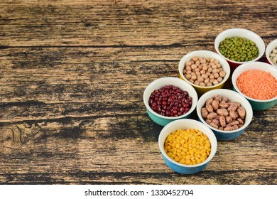 Legumes: dried beans and lentils variety on wooden background