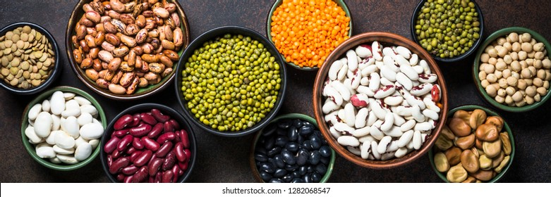 Legumes, lentils, chikpea and beans assortment in different bowls on stone table. Long banner format.