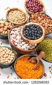 Legumes, lentils, chikpea and beans assortment in different bowls on white table close up.