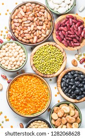 Legumes, lentils, chikpea and beans assortment in different bowls on white table top view.