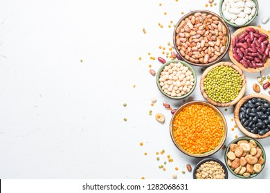 Legumes, lentils, chikpea and beans assortment in different bowls on white table. Top view with copy space.