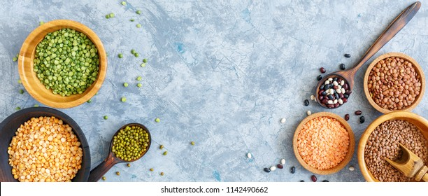 Legumes (lentils, mung beans,green and yellow split peas) in wooden bowls and spoons on a gray concrete background. Top view.