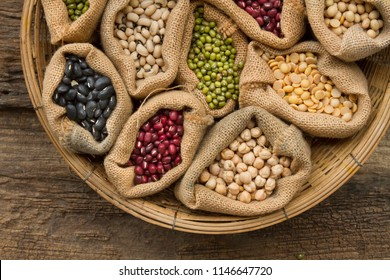 Legumes seed bean in sack bag on wooden background, top view. Dried food, Protein from plant, harvest concept.
