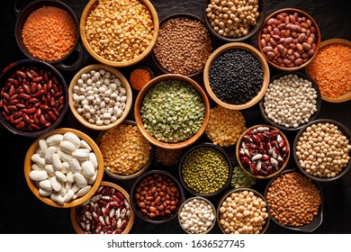 Legumes, a set consisting of different types of beans, lentils and peas on a black background, top view. The concept of healthy and nutritious food