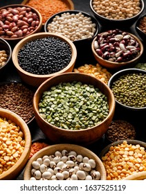 Legumes, a set consisting of different types of beans, lentils and peas on a black background, close up. The concept of healthy and nutritious food