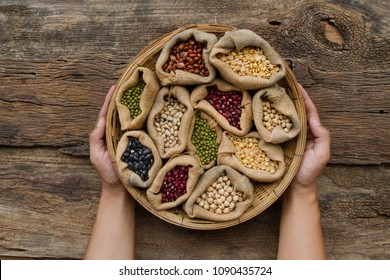legumes in wooden basket holding by hand on wooden background, top view