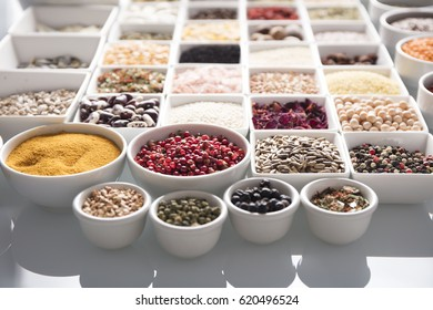 leguminous vegetables and spices in bowls, isolated on a white background