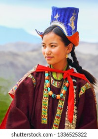 LEH, INDIA - JULY 01. Young unidentified girl dressed in traditional tibetan clothes poses fot a photo at the background of Himalaya mountains on July 01, 2018 in Leh, Ladakh, Jammu & Kashmir, India
