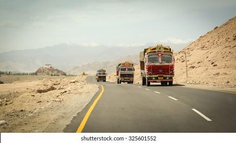 LEH, INDIA - JUNE 13, 2015. Tata trucks running pass the road on high altitude Ladakh-Leh road in Himalayan mountain, state of Jammu and Kashmir, India.