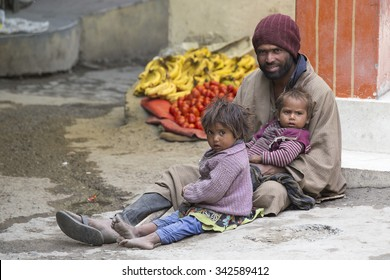 LEH, INDIA - JUNE 29, 2015: Unidentified poor Indian beggar family on street in Ladakh. Children of the early ages are often brought to the begging profession.