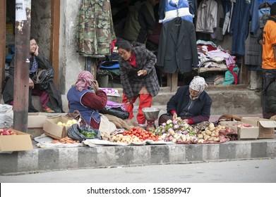 LEH, INDIA - OCTOBER 01: Market woman beside street selling vegetable and food in Leh, India. October 01, 2013