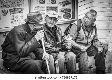 LEH, INDIA - October 2017: Tibetan people. Black and white photo of old Tibetan men sitting and talking outside on the street of Leh city, Ladakh, India
