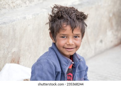 LEH, INDIA - SEPTEMBER 08 2014: Unidentified beggar boy begs for money from a passerby in Leh. Poverty is a major issue in India