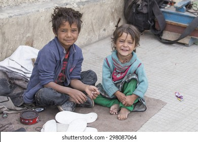 LEH, INDIA - SEPTEMBER 08, 2014 : An unidentified beggar girl and boy beg for money from a passerby in Leh. Poverty is a major issue in India