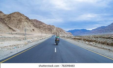 LEH, LADAKH, INDIA - JUL 12, 2016: A man riding on a bike on Manali Leh Highway. Adventure motorbike trips are very popular in Ladakh.