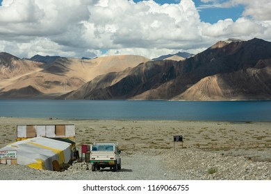 LEH LADAKH, INDIA - JULY 25: Camp and truck at view point of Pangong Lake with blue and turquoise water, Himalaya mountain, sky and cloud background in summer