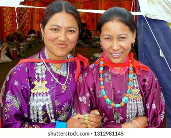 LEH, LADAKH / INDIA - JUNE 12, 2011: Two young Ladakhi women wear traditional silk costumes with rich silver, coral and turquoise jewellery, on June 12, 2011.