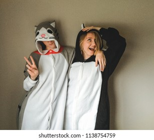 Lehi, UT / United States - May 13, 2016: Two best friends posing and laughing in animal onesies