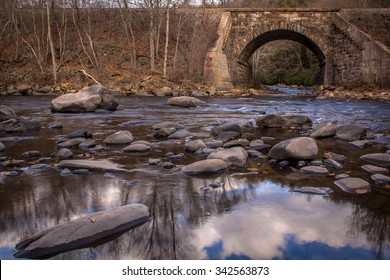 Lehigh Gorge State Park in late fall afternoon with old train tressel shown along reflective shallow river