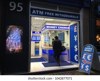 Leicester Square London,England,14 February 2018; Tourist pop in the money exchange shop with different currency coin and note for quick cash be aware of commission fee charge