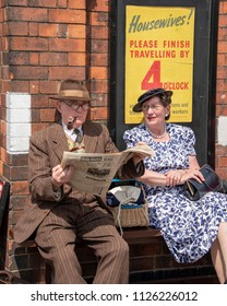 LEICESTERSHIRE,UK  - JUNE 03 2018:  Couple dressed in wartime clothing, wait at the station, during Victory Day Europe Celebration Event at Great Central Railway, Quorn