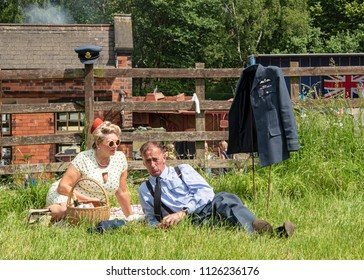 LEICESTERSHIRE,UK  - JUNE 03 2018: Couple dressed in wartime clothing, enjoy a picnic, during Victory Day Europe Celebration Event at Great Central Railway, Quorn